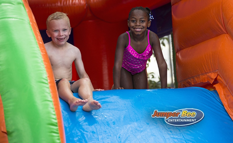 Two children playing on an inflatable water slide from Jumper Bee in Texas.
